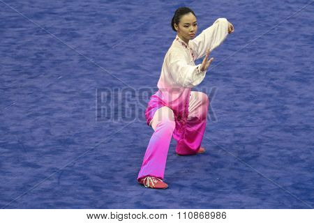 JAKARTA, INDONESIA: NOVEMBER 14, 2015: Lindswell Kwok from Indonesia performs the movements in the women's Taijiquan event at the 13th World Wushu Championship 2015 at Istoran Senayan.