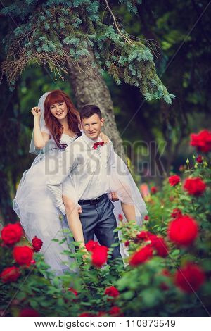 Portrait newlyweds among the blooming roses.