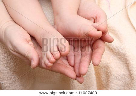 Children's Feet In The Hands Of The Mother
