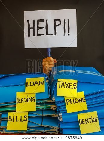 A Person Buried  Under A Pile Of Bill To Pay Asks  For Help With A Sign