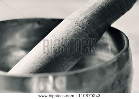 closeup of a tibetan singing bowl with its wooden mallet, in duotone