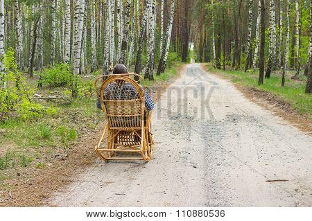 Elderly man is having rest in forest