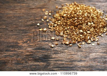 A pile of Gold nugget grains, on wooden background