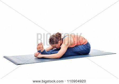 Sporty fit woman practices Ashtanga Vinyasa yoga back bending asana Paschimottanasana - seated forward bend isolated on white