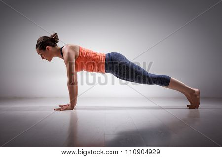 Beautiful sporty fit woman practices Ashtanga Vinyasa yoga Surya Namaskar Sun Salutation asana Utthita chaturanga dandasana - extended four-limbed pose