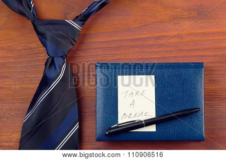 Neck tie near notepad with pen and yellow sticker with handwritten words Take A Break on wooden tabl