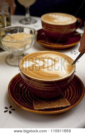 Two cups of cappuccino coffee with pattern in foam on table with sugar bowl