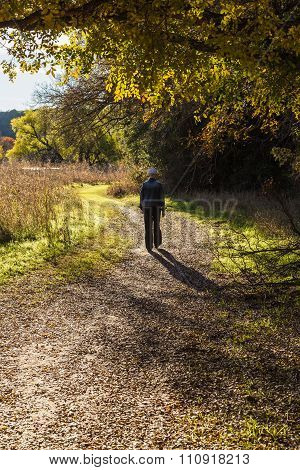 Senior Lady Walking On Rural Road