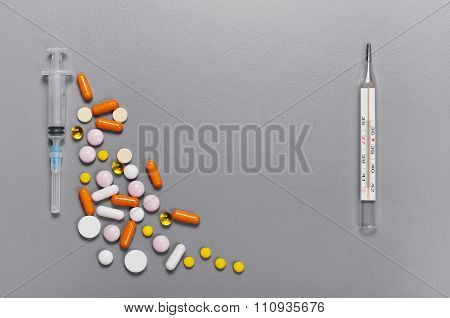 Scattered Pills, Capsules, Thermometer And Syringe