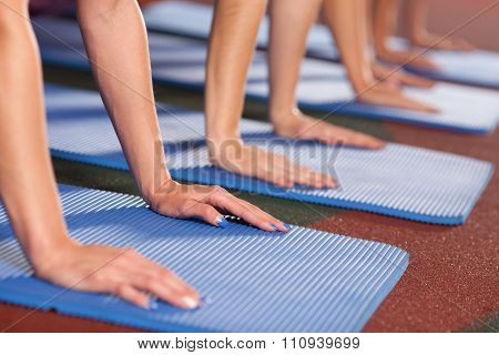 Woman's hands are placed on gym mat