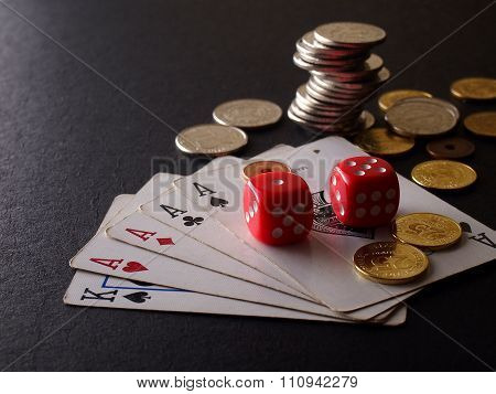 Two red dice, game cards and stack of coins