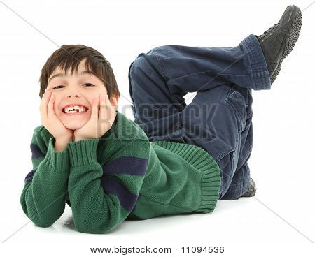 Adorable and very flexible 7 year old french american boy laying on belly with legs twisted behind him. Smiling. poster