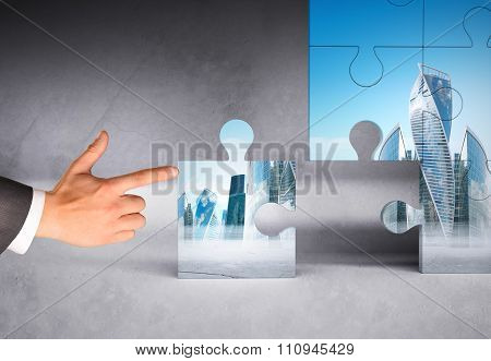 Man hand pushing puzzle piece of modern city