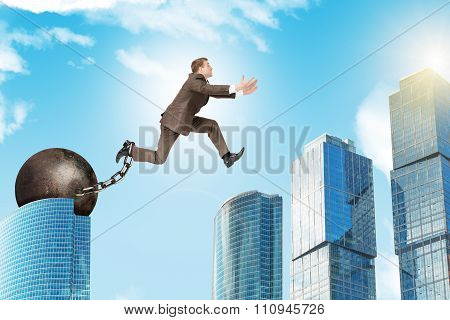 Man in suit with iron ballast hopping over city