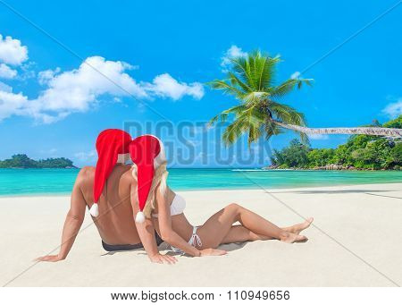 Couple In Christmas Santa Hats At Tropical Palm Sandy Beach