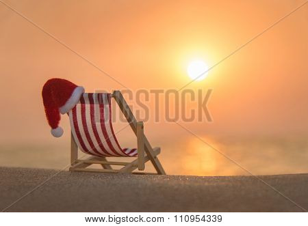 Deckchair With Christmas Santa Hat At Ocean Beach During Sunset