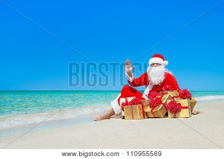 Christmas Santa Claus With Gift Boxes Resting At Ocean Beach
