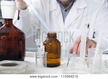 Microbiologist Hand Cultivating Whit Inoculation Loops In Pipette Close-up.