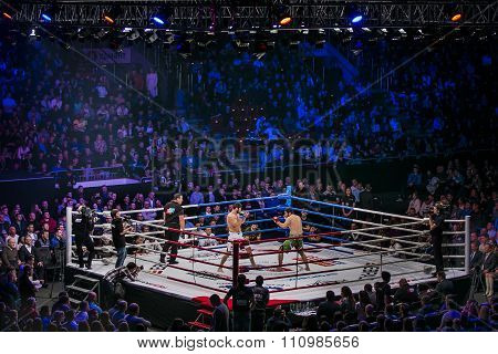 General plan of sports arena during fight in ring, fighters and referee across ring fans