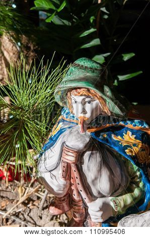 Painted pottery statue of a man playing the characteristic zampogna in the ceramic nativity scene of an artisan in Caltagirone poster