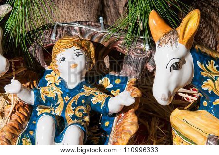 Painted pottery statue portraying baby Jesus in the ceramic nativity scene of an artisan in Caltagirone poster