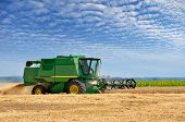 Agricultural machinery harvests of cereal crops in the field poster