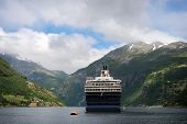 Big cruise ship attached to a buoy in the water of the narrow Geirangerfjord surrounded by mountains in Møre og Romsdal Norway. poster