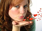 Pretty young woman blowing a kiss with hearts swirling poster