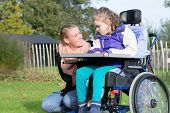 Disability a disabled child in a wheelchair relaxing outside together with a carer poster