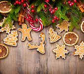 Christmas Holiday Background with various Gingerbread cookies, Candy Cane and evergreens border over wooden table. Christmas and New year food. Christmas decoration and sweets on wood background poster