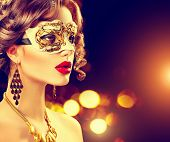 Beauty model woman wearing venetian masquerade carnival mask at party over holiday dark background with magic glow. Christmas and New Year celebration. Glamour lady with perfect make up and hairstyle poster