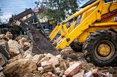 bulldozer loading demolition debris and concrete waste for recycling at construction site poster