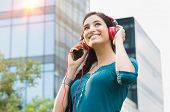Closeup shot of young woman listening to music with mobile phone in the city center. Happy smiling girl listening to music with professional red headset. Beautiful brunette  young woman feeling free. poster