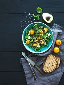 Bowl of green salad with avocado, arugula, cherry tomatoes and sunflower seeds, grilled bred slices, fresh herbs over black wooden backdrop, top view poster