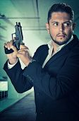 Male agent in an alert position and loading the chamber of his handgun poster