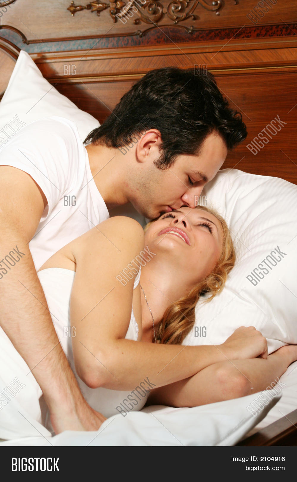 Couple kissing and hugging on bed