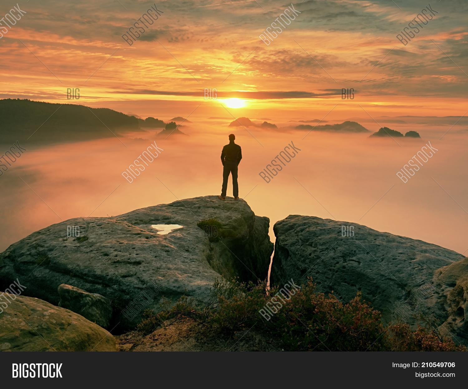 Man stands alone on the peak of rock hiker watching to autumn sun at horizon