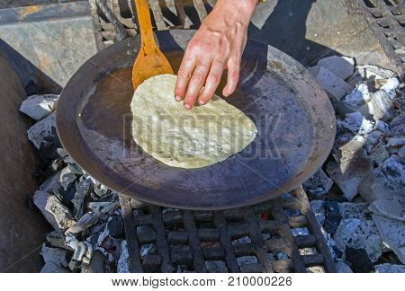 Frying pan with pancake on the stove with coals