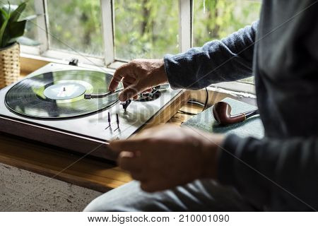 Hands insert vinyl disc to turntable player