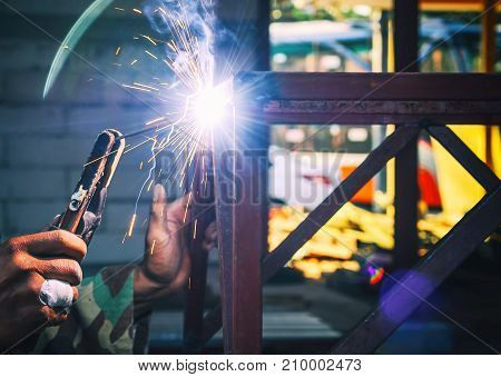 Workers welding steel structure to assemble parts of the steel structure.