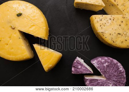 Assortment of dairy gourmet milk products, top view. Quality sorts of winery cheese and Caciotta with herbs and pistachio