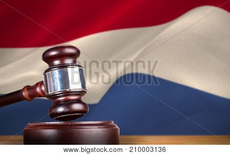 Hammer and gavel against 3d digitally generated dutch national flag