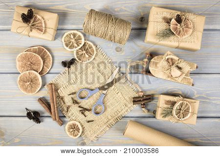 Aged Photo, Accessories, Decoration And Wrapped Gifts For Christmas With Wooden Sled On Old Boards