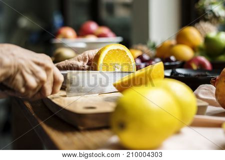 Closeup of hand with knife cutting orange