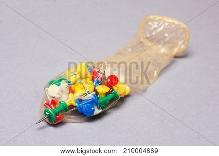 Condom and office pin on a gray background. Broken pierced condom. Checking or testing a condom