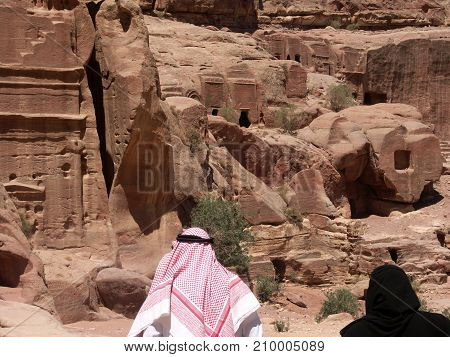 Arabic tourist couple with man wearing a shemagh watching the ruins of Petra in Jordan