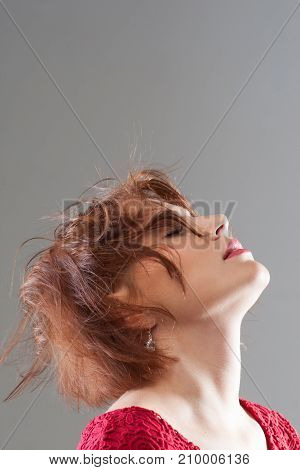Feeling of freedom and pleasure. Female hairstyle advertising. Creative woman haircut closeup on grey background with free space, pleasant concept