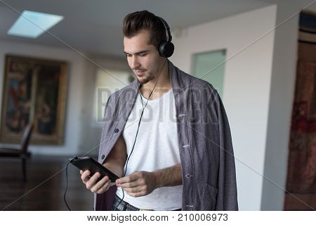 Casual caucasian man listening music on winter day indoor