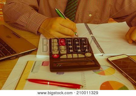 view of bookkeeper or financial inspector hands making report calculating or checking balance. Home finances investment economy saving money or insurance concept - Retro color