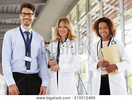 Portrait of three male and female doctors, looking to camera